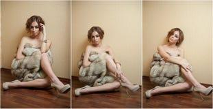 Mujer joven atractiva atractiva envuelta en un abrigo de pieles que se sienta en el piso en la habitación El estar femenino del p Imagen de archivo