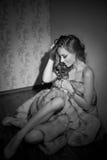 Mujer joven atractiva atractiva envuelta en un abrigo de pieles que se sienta en la habitación Retrato blanco y negro de soñar de Fotos de archivo libres de regalías
