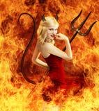 Mujer joven atractiva como diablo en fuego Imagen de archivo libre de regalías