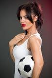 Mujer joven atractiva con el balón de fútbol Imagenes de archivo