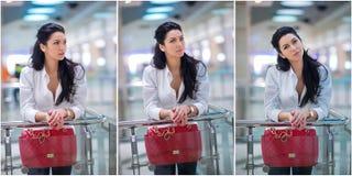 Mujer joven atractiva con el bolso rojo en centro comercial Señora joven de moda hermosa con el pelo largo en la camisa masculina Foto de archivo
