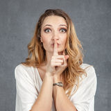 Mujer joven atractiva con el finger en los labios Imágenes de archivo libres de regalías