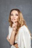 Mujer joven atractiva con el finger en los labios Fotografía de archivo