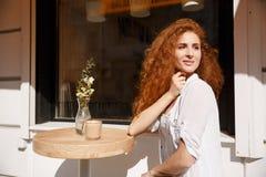 Mujer joven atractiva con el pelo rizado que se sienta en la tabla Fotografía de archivo