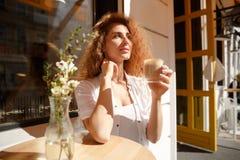 Mujer joven atractiva con el pelo rizado que se sienta en la tabla Imagen de archivo libre de regalías