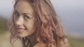 Mujer joven atractiva con el pelo rizado rosado que se sienta en el parapeto y la presentación metrajes