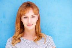 Mujer joven atractiva con el pelo rojo que mira fijamente por la pared azul Fotografía de archivo libre de regalías