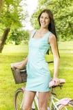 Mujer joven atractiva con la bicicleta Imagen de archivo libre de regalías