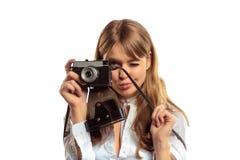 Mujer joven atractiva con la cámara de la foto del vintage que hace el lanzamiento Fotografía de archivo