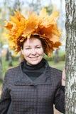 Mujer joven atractiva con la guirnalda del arce que coloca el árbol de abedul cercano Fotos de archivo