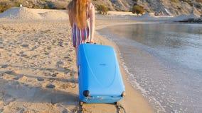 Mujer joven atractiva con la maleta en la playa almacen de video