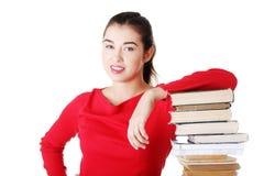 Mujer joven atractiva con la pila de libros. Fotos de archivo