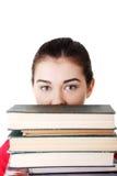 Mujer joven atractiva con la pila de libros. Fotografía de archivo libre de regalías