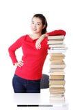 Mujer joven atractiva con la pila de libros. Fotografía de archivo