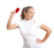 Mujer joven atractiva con la tarjeta de crédito roja en blanco Foto de archivo