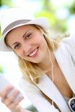 Mujer joven atractiva con los auriculares que habla en el teléfono Fotos de archivo libres de regalías