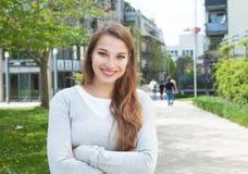 Mujer joven atractiva con los brazos cruzados en ropa casual afuera Imagen de archivo