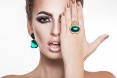 Mujer joven atractiva con los diamantes verdes en lookin de los accesorios imagen de archivo