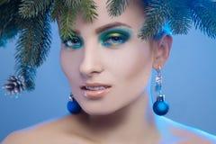 Mujer joven atractiva con maquillaje agradable y el árbol de navidad encendido él Imagenes de archivo