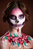 Mujer joven atractiva con maquillaje del cráneo del azúcar Foto de archivo