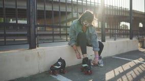 Mujer joven atractiva con patinaje sobre ruedas en la calle, teniendo timen de la diversión en la puesta del sol almacen de video