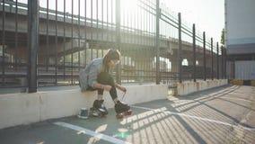 Mujer joven atractiva con patinaje sobre ruedas en la calle, teniendo timen de la diversión en la puesta del sol metrajes