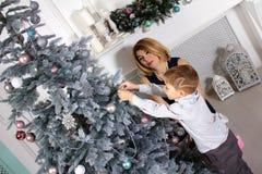 Mujer joven atractiva con su hijo adornar el árbol de navidad en casa que se prepara para la celebración de Navidad fotografía de archivo