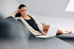 Mujer joven atractiva con un ordenador portátil que se sienta en un sofá Fotografía de archivo