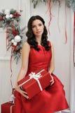 Mujer joven atractiva con un regalo de la Navidad fotografía de archivo