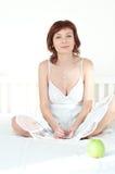 Mujer joven atractiva con una manzana y un gla verdes fotos de archivo