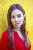 Mujer joven atractiva, contra la perspectiva de la pared amarilla Imagenes de archivo