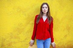 Mujer joven atractiva, contra la perspectiva de la pared amarilla Foto de archivo
