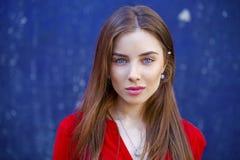 Mujer joven atractiva, contra la perspectiva de la pared azul marino Foto de archivo