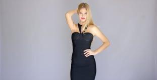 Mujer joven atractiva Curvaceous que presenta en vestido elegante foto de archivo