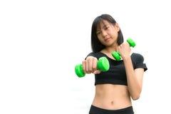 Mujer joven atractiva de la aptitud que lleva a cabo pesas de gimnasia aisladas Fotografía de archivo