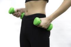Mujer joven atractiva de la aptitud que lleva a cabo pesas de gimnasia aisladas en whi Foto de archivo