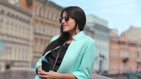 Mujer joven atractiva de la moda en gafas de sol que disfruta de luz del sol en el fondo constructivo histórico almacen de video