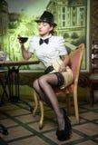 Mujer joven atractiva de moda con el equipo masculino, el arco y las medias negras sentándose en restaurante Señora hermosa Posin Imagen de archivo libre de regalías