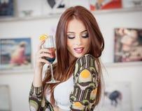 Mujer joven atractiva de moda en el vestido coloreado que celebra un vidrio y una sonrisa Pelirrojo hermoso que presenta en paisa Imagen de archivo