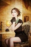 Mujer joven atractiva de moda en el vestido negro que se sienta en restaurante Presentación morena hermosa en paisaje elegante de Fotografía de archivo libre de regalías
