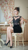 Mujer joven atractiva de moda en el vestido negro que se sienta en restaurante Presentación morena hermosa en paisaje elegante de Imagen de archivo libre de regalías
