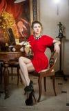 Mujer joven atractiva de moda en el vestido rojo que se sienta en restaurante Señora hermosa que presenta en paisaje elegante del Foto de archivo