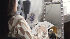 Mujer joven atractiva del diseñador de moda que trabaja en el estudio del arte Las miradas de una mujer joven en los bosquejos de almacen de metraje de vídeo
