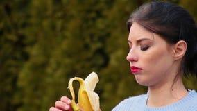 Mujer joven atractiva atractiva del primer con el pelo oscuro y los labios rojos en la chaqueta azul que pela el plátano y que lo