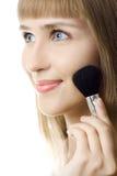 Mujer joven atractiva del retrato que aplica blusher Foto de archivo