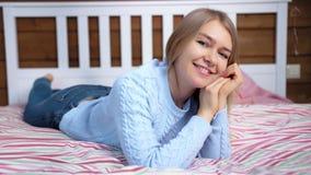 Mujer joven atractiva del tiro lleno que disfruta del fin de semana que miente en cama en el dormitorio acogedor que mira la cáma almacen de video