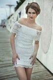 Mujer joven atractiva elegante magnífica en el vestido blanco del cordón que presenta bastante Fotos de archivo libres de regalías