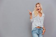 Mujer joven atractiva emocionada que señala lejos Foto de archivo