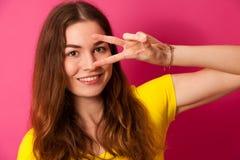 Mujer joven atractiva en camiseta amarilla sobre backg rosado vibrante Fotos de archivo libres de regalías