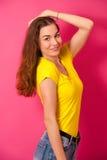 Mujer joven atractiva en camiseta amarilla sobre backg rosado vibrante Imagen de archivo